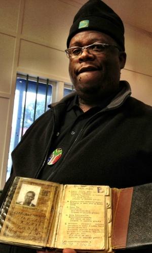 Habitante do bairro de Langa, na Cidade do Cabo, mostra o documento que a população negra tinha que carregar para poder se locomover durante a época do apartheid