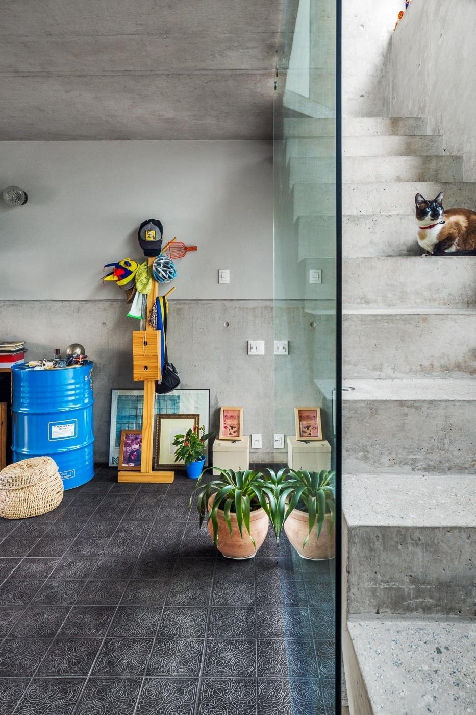 Peças garimpadas compõem o recanto da sala de jantar que tem piso de ladrilho hidráulico, da Ladrilhar. Destaque para o tonel azul, comprado em um posto de gasolina, usado como mesa lateral. À direita está a escada que dá acesso ao segundo pavimento, com o dormitório e o banheiro. O apê Vila Aspicuelta foi decorado pelos arquitetos Rafael Loschiavo e Veronica Molina