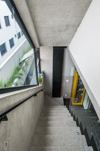 A escada que liga o primeiro e o segundo pavimento possui guarda-corpo estrutural de concreto de um lado (à esq.) e vidro sustentado por ferragens articuladas, de outro. No pé da escadaria, a cristaleira amarela foi comprada na Retrô 63. O apê Vila Aspicuelta foi decorado pelos arquitetos Rafael Loschiavo e Veronica Molina