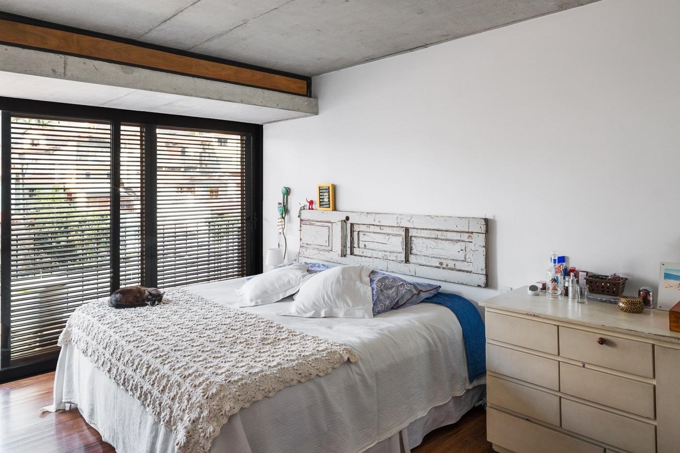 No segundo pavimento, o dormitório é igualmente repleto de luz natural, somente quebrada pela porta veneziana, feita de madeira. Destaque para a cabeceira da cama,
