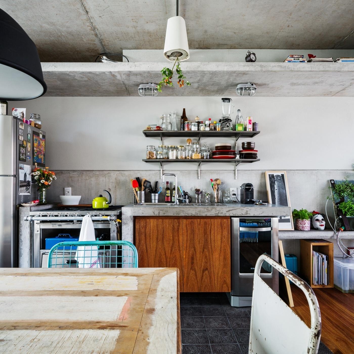 Integrada aos espaços de estar e jantar, a cozinha do apê Vila Aspicuelta, com decoração dos arquitetos Rafael Loschiavo e Veronica Molina, exibe o mesmo ar rústico descontraído dos demais ambientes sociais. Nela, são combinados à bancada de concreto com gabinete de madeira, um fogão com aspecto industrial, da Sufilsa, e as prateleiras da Ominia