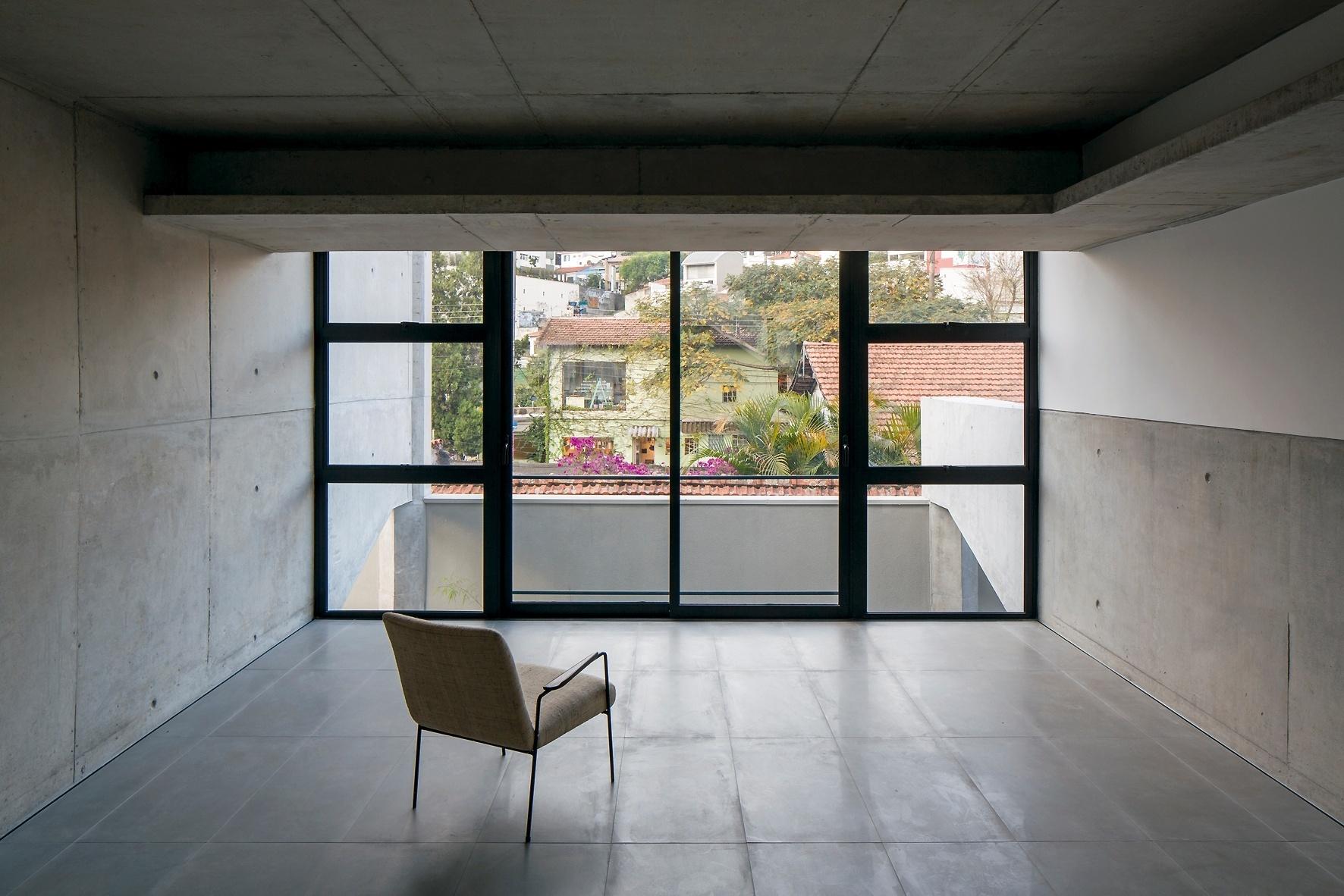 O espaço da sala de estar de uma das unidades do condomínio Vila Aspicuelta é totalmente voltado para o exterior, o que favorece a ventilação e a iluminação naturais, além de oferecer vistas para o entorno da Vila Madalena, em São Paulo. Na estrutura, destaque para as vigas invertidas de transição (externas) que repousam sobre pilares embutidos no muro. O projeto é do escritório Tacoa Arquitetos