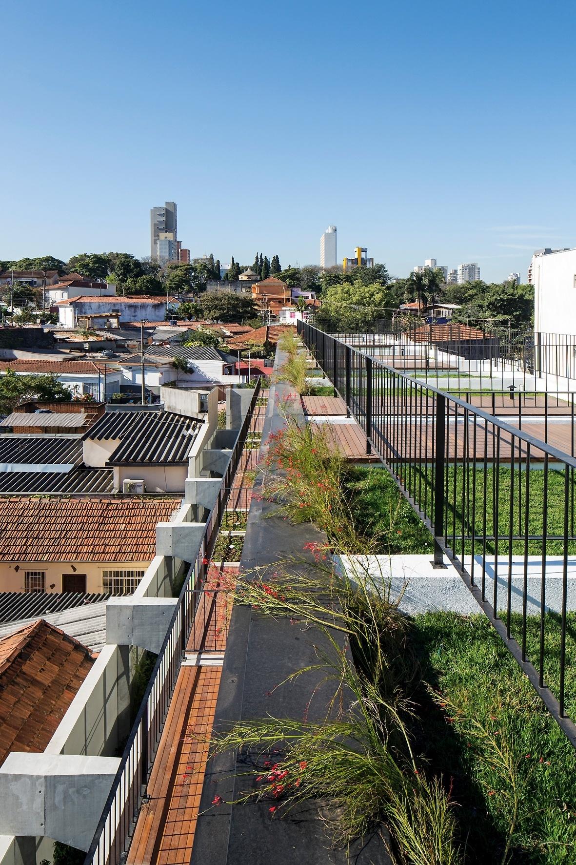 Desse ângulo, vê-se a sequência de terraços das oito unidades do predinho chamado Vila Aspicuelta, projetado pelo escritório Tacoa Arquitetos, e, ainda, as vigas de transição que repousam sobre pilares embutidos no muro lateral (à esq.). No entorno, a paisagem da Vila Madalena, em São Paulo