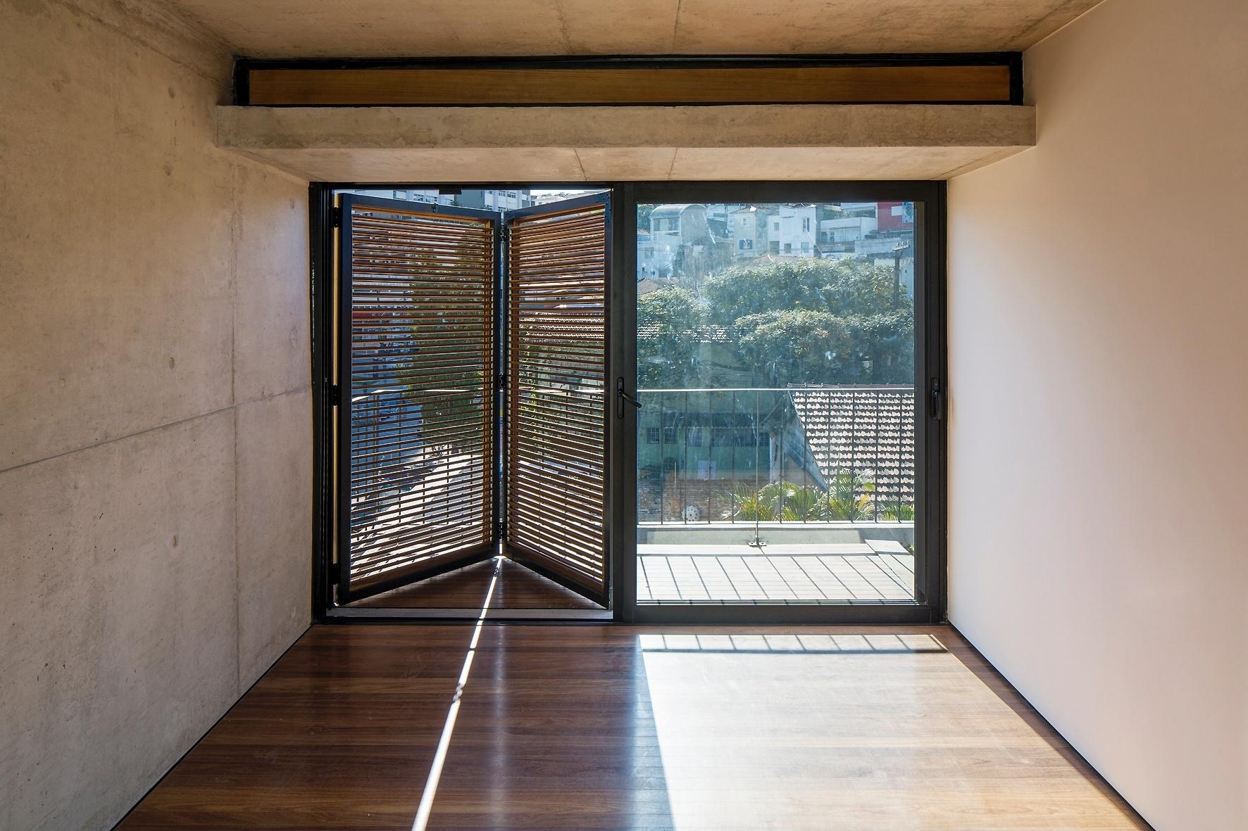 No segundo andar, o espaço do dormitório se abre para um terraço e recebe ventilação cruzada à partir da abertura basculante na parte superior da laje. A veneziana em madeira controla a luminosidade natural dos cômodos do Vila Aspicuelta, condomínio pequeno projetado pelo escritório Tacoa Arquitetos, em São Paulo