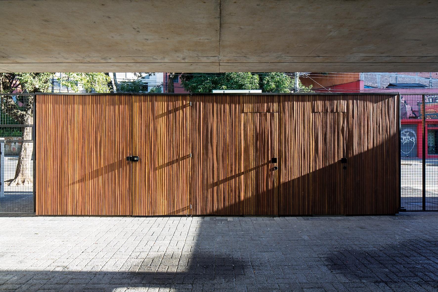 O volume da entrada do Vila Aspicuelta, projetado por Tacoa Arquitetos, abriga vários espaços como portaria, banheiro para os funcionários, hidrômetros e áreas técnicas, além da passagem de pedestres. Em ripas de freijó e com secção quadrada, o bloco contrasta com o concreto predominante da edificação