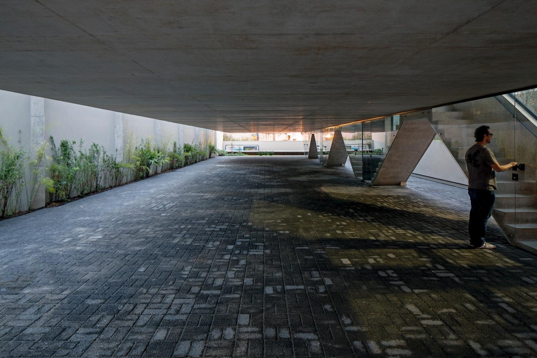 O estacionamento do Vila Aspicuelta, projetado pelo escritório Tacoa Arquitetos, se apresenta como a rua de uma vila, com piso formado por blocos drenantes de concreto. Cada uma das oito casas/ apês possui entrada independente
