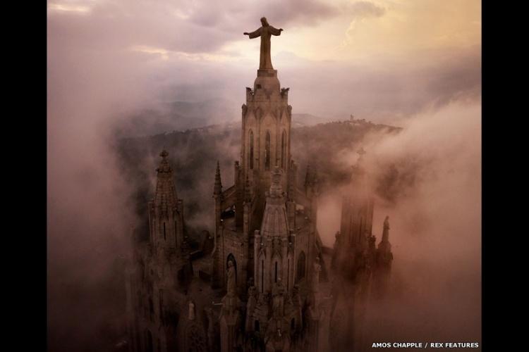 Nuvens circundam os pilares da Igreja do Sagrado Coração, no alto de uma colina, também em Barcelona