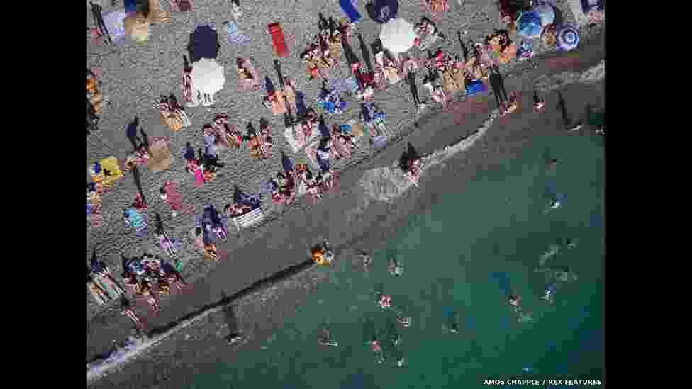 O fotógrafo neo-zelandês Amos Chapple usou uma câmera acoplada a um drone para tirar fotos aéreas de alguns dos mais belos pontos turísticos da Europa. Ao lado, vários turistas se banham em uma praia no Mar Negro, na Abecásia (território autônomo na Geórgia). - Amos Chapple/Rex Features
