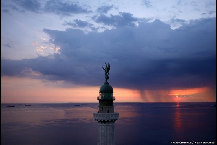 O pôr do sol no Farol da Vitória, no Golfo de Trieste, na Itália