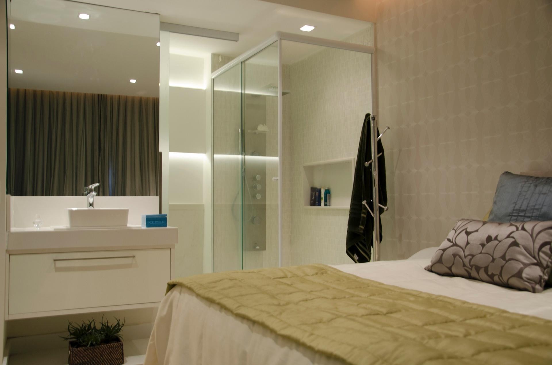 A segunda grande mudança estrutural no apê Icaraí, com projeto do escritório Ravaglia & Philot, foi a integração do banheiro ao quarto. O sanitário fica reservado em um dente, atrás da bancada, enquanto a cuba e o boxe, este com portas de vidro temperado, voltam-se para o dormitório, diretamente. O piso vinílico, resistente e lavável, com textura de madeira substituiu os tacos originais. Na área molhada, o chão leva porcelanato branco piguês (90 cm x 90 cm) e as paredes têm pastilhas