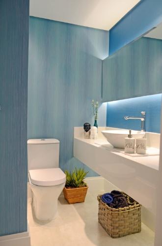 No lavabo, duas fitas de LEDs acompanham o comprimento da bancada e ficam escondidas atrás do espelho, que se destaca da parede pela iluminação indireta, ganhando volume. Também por trás do espelho está um spot para lâmpada AR-70 que tem facho de luz direcionado para a cuba (Bello Banho). O papel de parede é da Orlean e o projeto de interiores é assinado pelo escritório Ravaglia & Philot