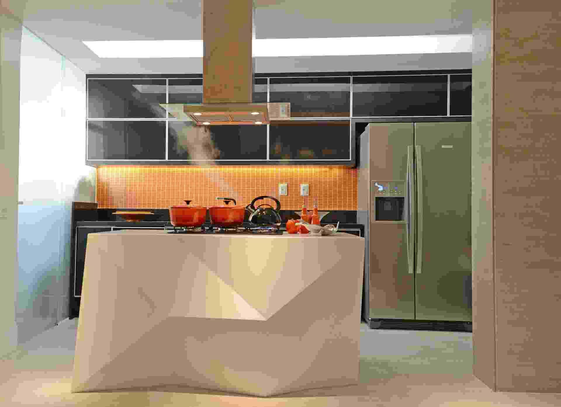 A ilha de cocção, com design do escritório Ravaglia & Philot - que também assina os interiores do apê Icaraí -, foi feita em Corian (Don Artesano) e centraliza a integração entre cozinha e as salas de estar e jantar. As paredes da cozinha receberam porcelanato (30 cm x 60 cm) e pastilhas (2 cm x 2 cm) da Portobello. Um rasgo no rebaixo de gesso (ao fundo) garante luminosidade uniforme e indireta, enquanto fitas de LEDs foram inseridas na marcenaria preta para destacar a cor das patilhas - Cinthia Serrano/ Divulgação
