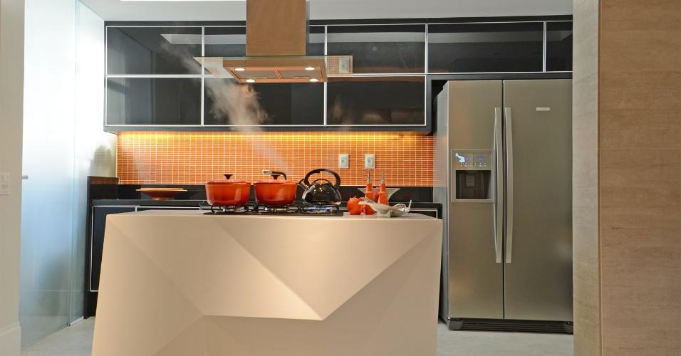 A ilha de cocção, com design do escritório Ravaglia & Philot - que também assina os interiores do apê Icaraí -, foi feita em Corian (Don Artesano) e centraliza a integração entre cozinha e as salas de estar e jantar. As paredes da cozinha receberam porcelanato (30 cm x 60 cm) e pastilhas (2 cm x 2 cm) da Portobello. Um rasgo no rebaixo de gesso (ao fundo) garante luminosidade uniforme e indireta, enquanto fitas de LEDs foram inseridas na marcenaria preta para destacar a cor das patilhas