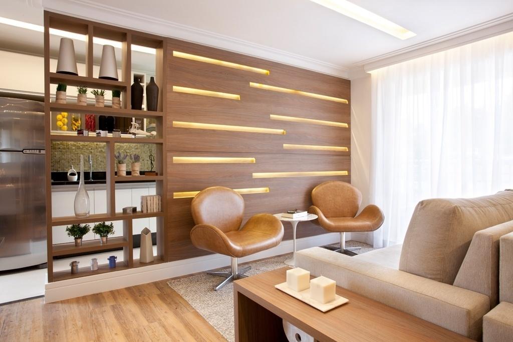Neste projeto da arquiteta Adriana Fontana, a aliada para dividir o estar da cozinha, de forma a manter a conexão entre os dois ambientes, foi a marcenaria. Veja que os nichos no painel de madeira promovem a transparência mas preservam a privacidade de quem está na sala