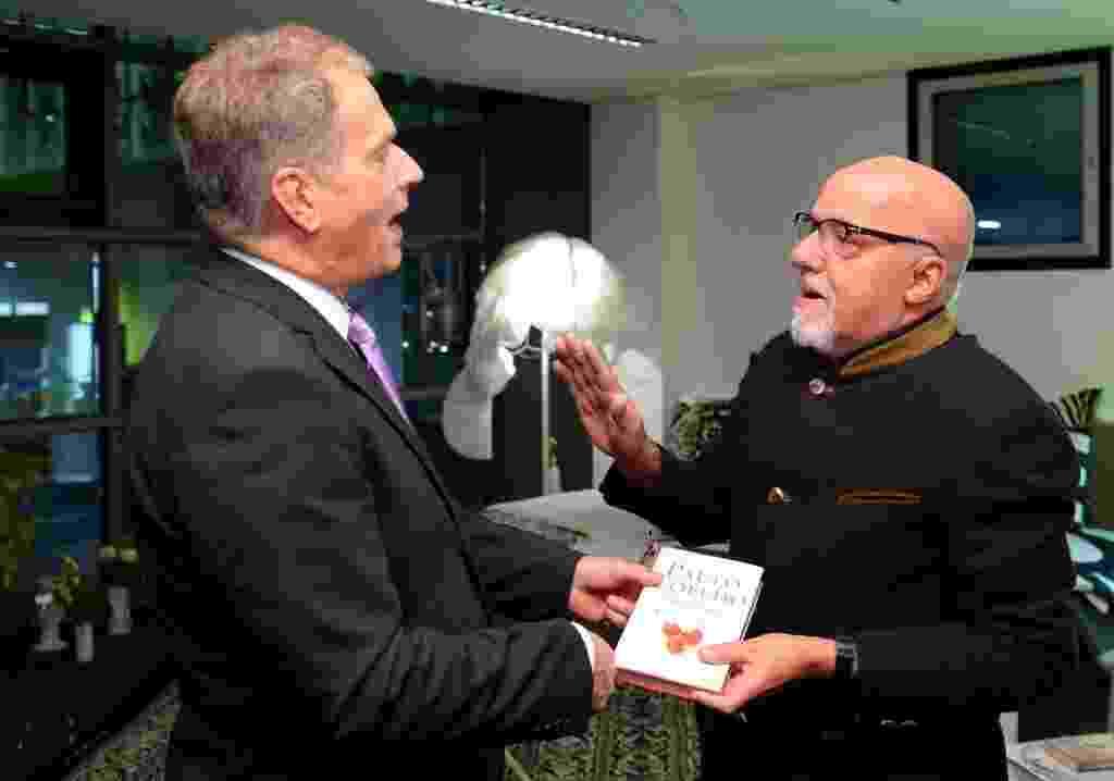 07.out.014 - O presidente da Finlândia, Sauli Niinisto, e o escritor Paulo Coelho conversam durante abertura da Feira do Livro de Frankfurt - AFP