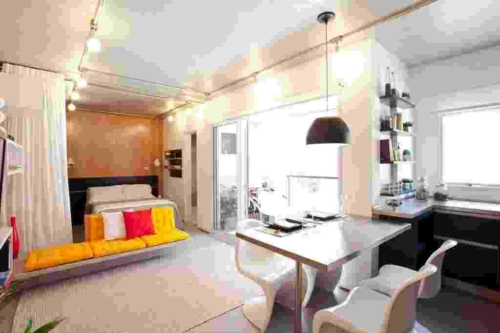O sofá de alvenaria coberto por futons amarelos não impede a integração dos ambientes, mas marca a separação da área do dormitório, que pode ser isolada do estar pela cortina branca (na foto, recolhida à esquerda). O projeto do Estúdio Option é assinado pelo escritório FGMF - Fran Parente/ Divulgação