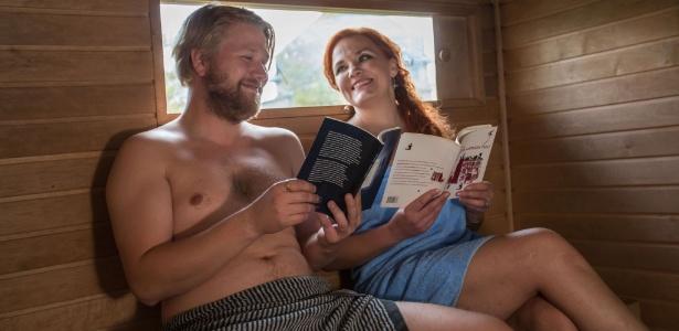 Os autores Harri Hertell e Katariina Vuorinen fazem leitura em uma sauna móvel na Feira do Livro de Frankfurt. Finlândia é a homenageada deste ano do evento literário - Frank Rumpenhorst/AFP