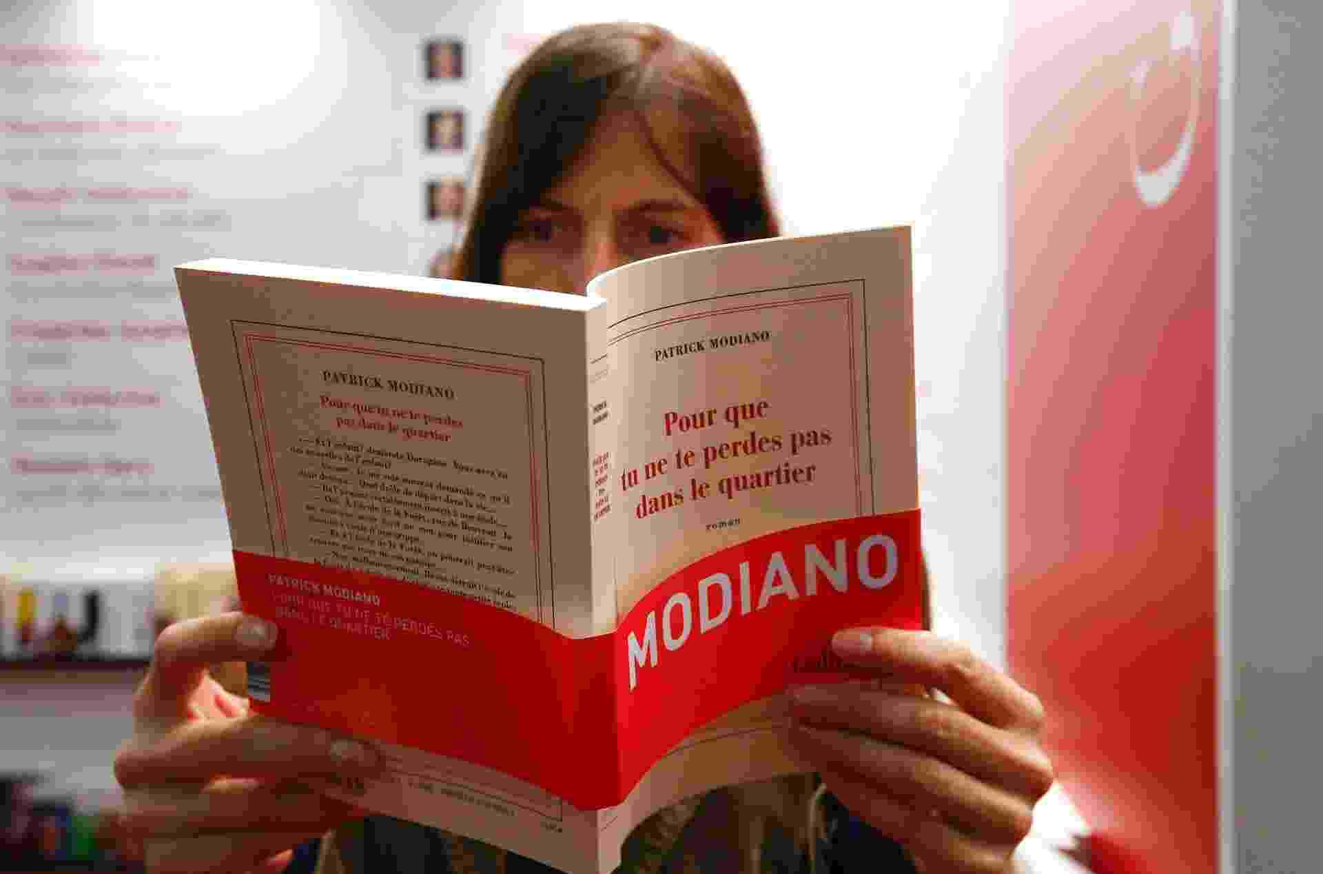 9.out.2014 - Mulher lê livro de Patrick Modiano durante a Feira de Frankfurt - Reuters