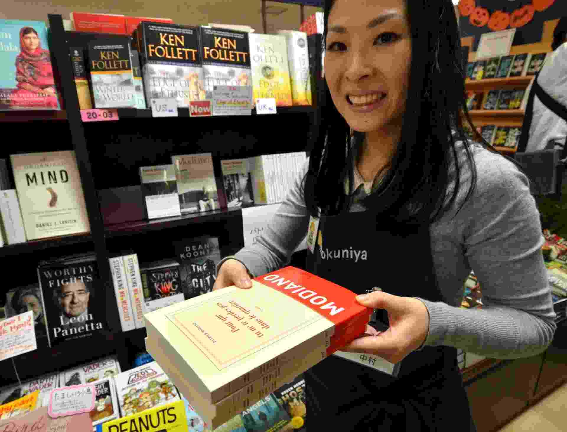 9.out.2014 - Vendedora de livraria em Tóquio mostra obra de Patrick Modiano, vencedor do Nobel de Literatura - Yoshikazu Tsuno/AFP