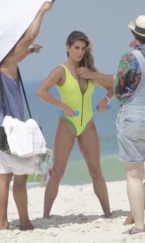 10.out.2014 - Membro da equipe ajeita cabelos de Deborah Secco enquanto ela posa em praia da Barra da Tijuca, no Rio de Janeiro