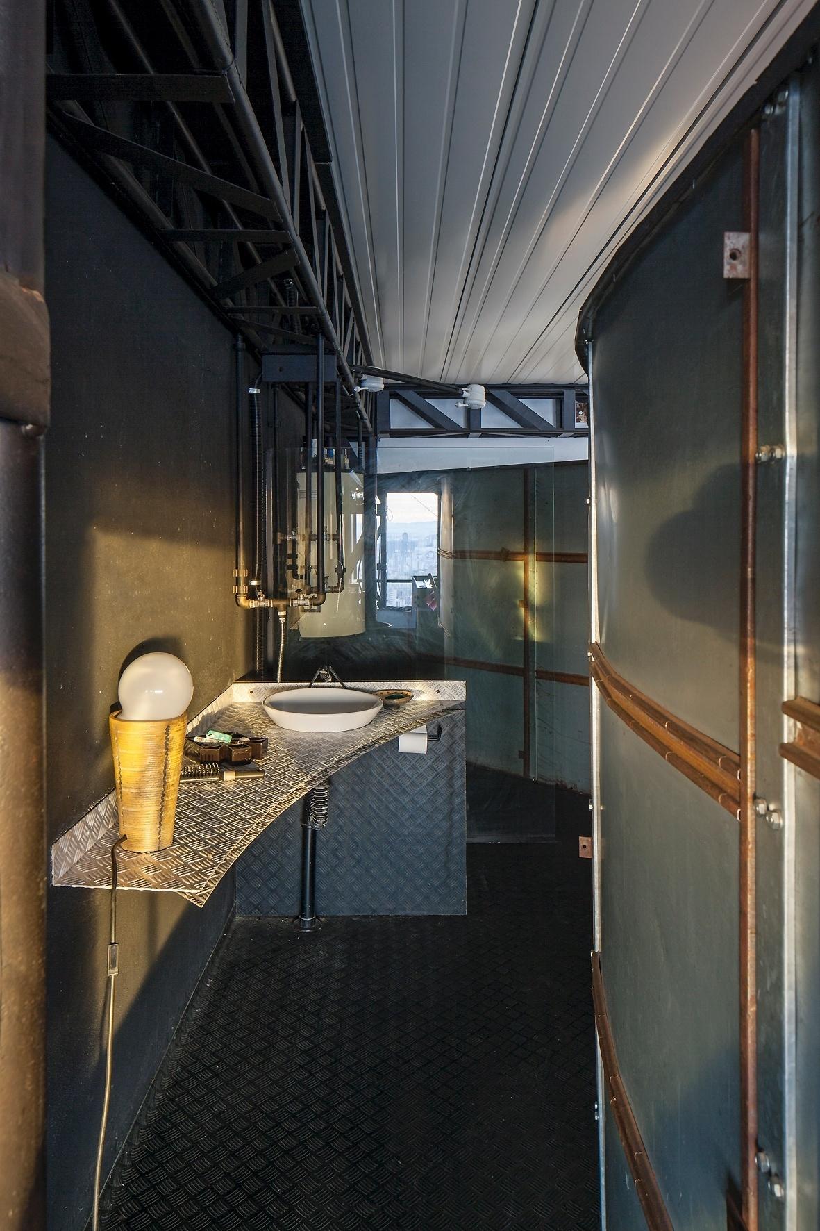 O banheiro do casal utiliza materiais de demolição, como o piso em chapas de aço revestidas com borracha, paredes metálicas a partir de embalagens usadas e bancada da pia em alumínio. A casa Mangabeiras foi projetada pelo arquiteto Allen Roscoe
