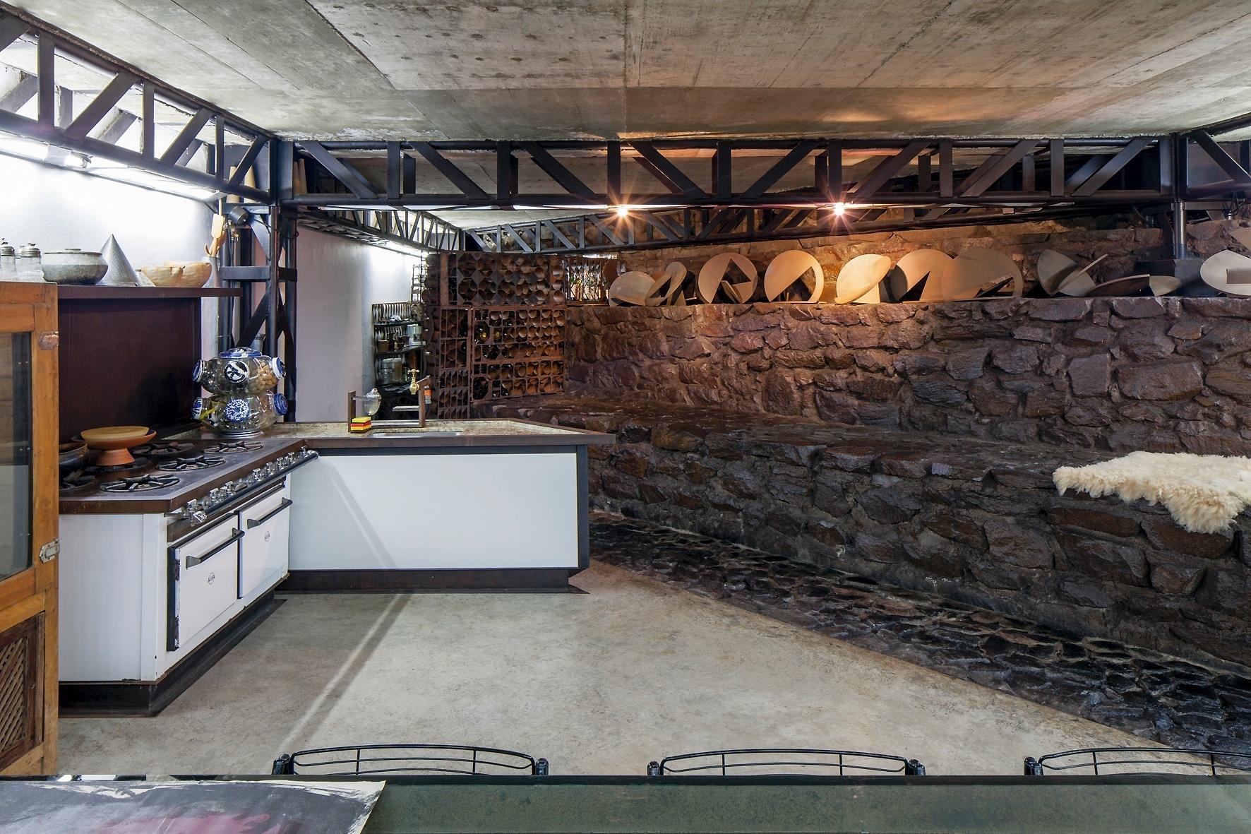 As pedras da região comparecem de modo marcante na casa Mangabeiras, projeto do arquiteto Allen Roscoe. Como no subsolo, onde a adega divide espaço com a cozinha. Destaque para o sistema hidráulico aparente com mangueiras flexíveis que permitem a movimentação da pia para qualquer local do ambiente