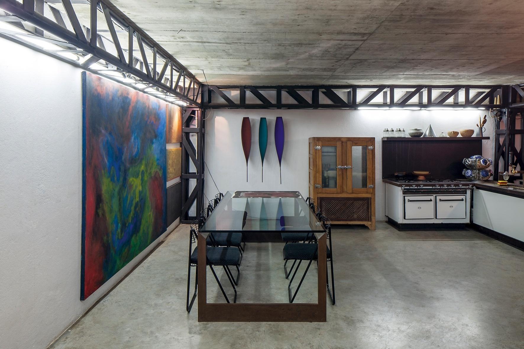 No subsolo encontram-se a cozinha com mesa para refeições, depósito e adega. As paredes exibem obras de arte de amigos de Allen Roscoe, arquiteto autor do projeto da casa Mangabeiras