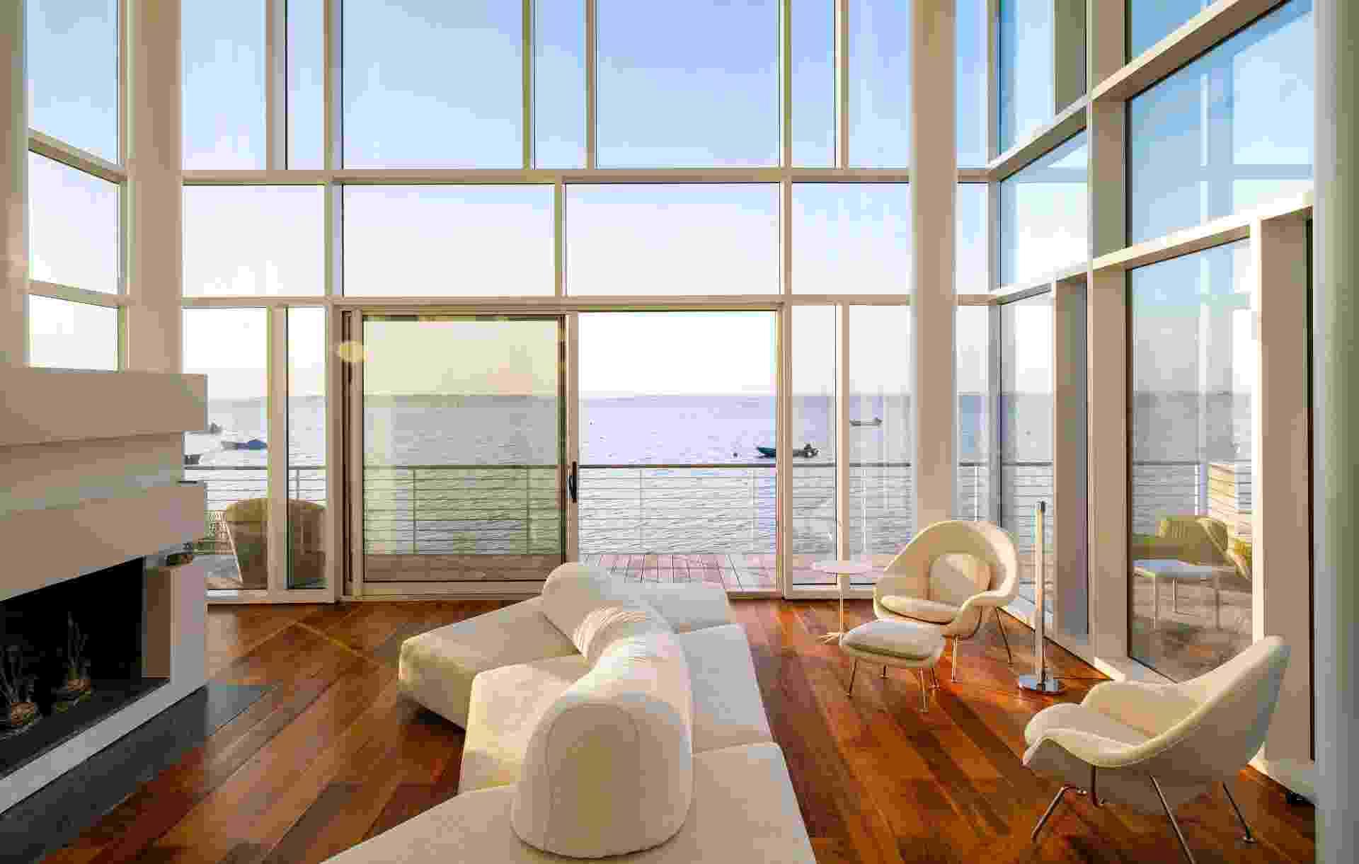 """A bela casa de praia em Fair Harbor, nos EUA, foi construída basicamente com aço e vidro. As """"paredes"""" são compostas em parte por três linhas de janelas. Na iluminada sala de estar, destaque para as poltronas Womb (à dir.), desenhadas por Eero Saarinen (Imagem do NYT, usar apenas no respectivo material) - Trevor Tondro/ The New York Times"""