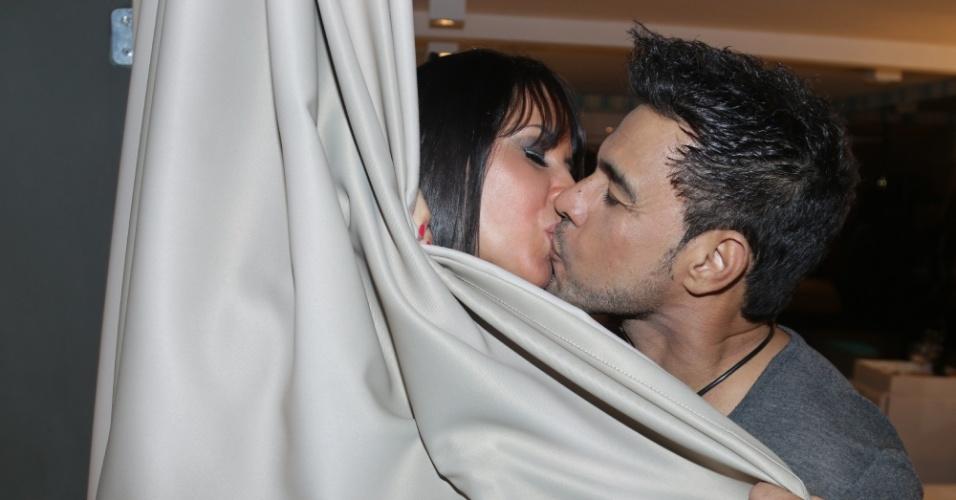 16.out.2014 - Cobertos por uma cortina, Zezé Di Camargo e Graciele Lacerda, sua namorada, trocam beijos durante inauguração de um motel em Curitiba