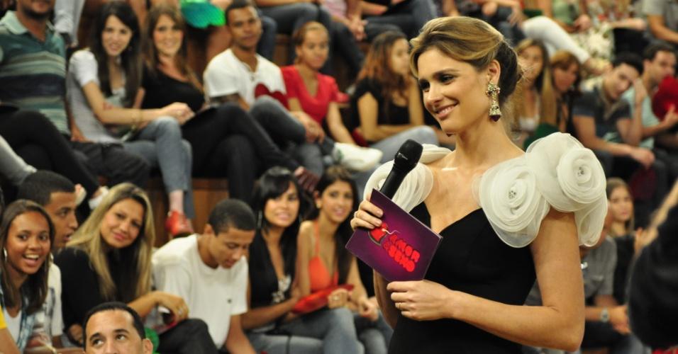 Fernanda Lima usa vestido preto com aplicações de flores de tecidos nas mangas durante o