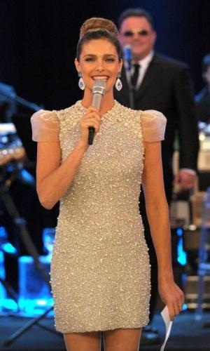 Com um vestido marfim com aplicações, brincão e os cabelos presos com um coque, Fernanda Lima apresenta temporada de 2012 de