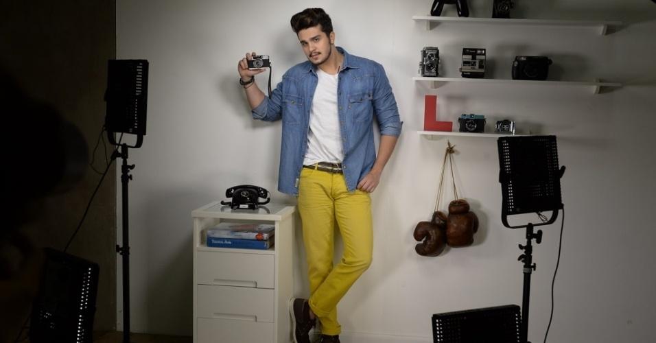 18.out.2014 - De camisa jeans e calça amarela, Luan Santana posa com câmera analógica para campanha de moda