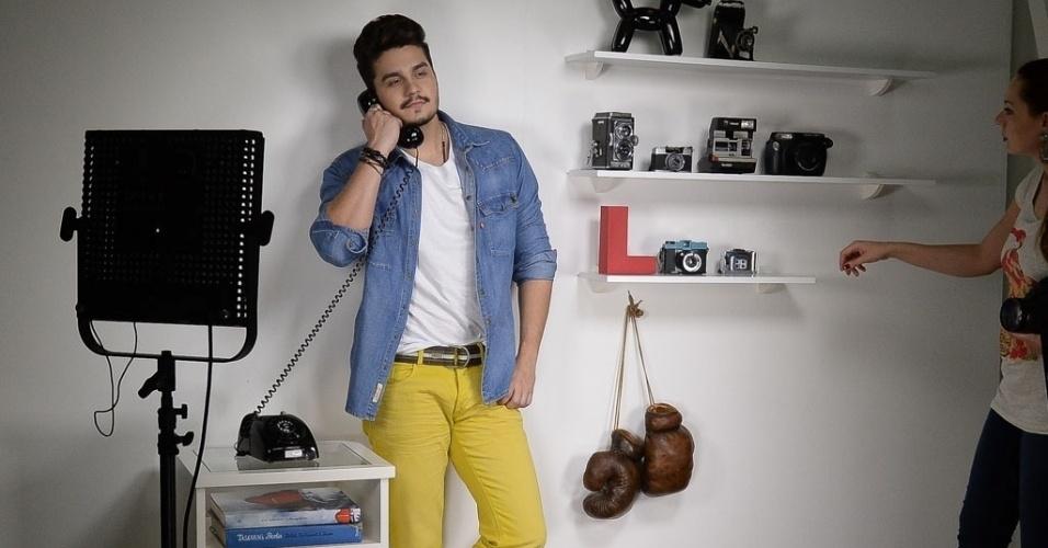 18.out.2014 - De camisa jeans e calça amarela, Luan Santana posa com telefone antigo para campanha de moda