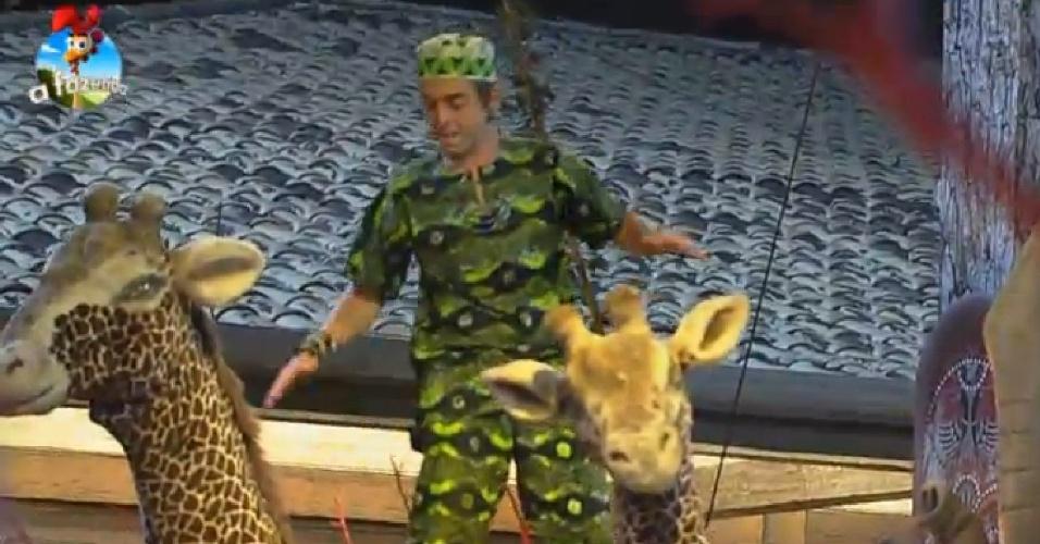 18.out.2014 - Diego DH fica em pé em cima de girafa cenográfica durante a Festa África