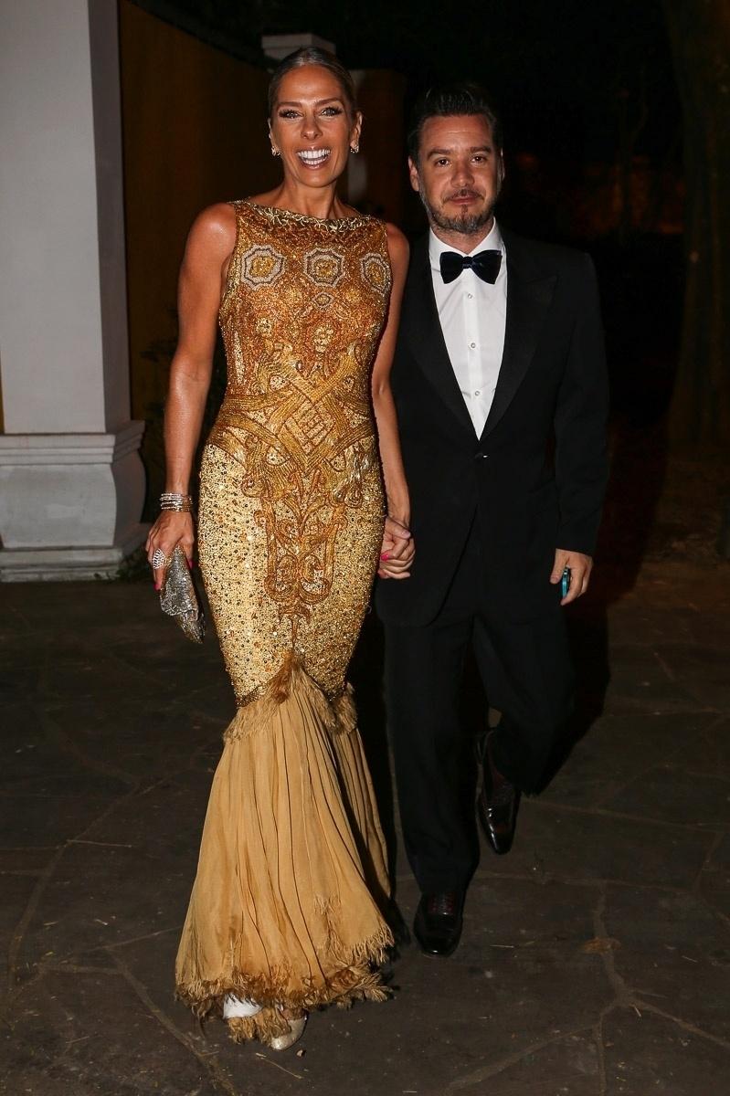 18.out.2014 - Adriane Galisteu e o marido, Alexandre Iódice, chegam para o casamento do jornalista Bruno Astuto e do estilista Sandro Barros, em São Paulo
