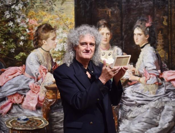 """O guitarrista Brian May, ex-Queen, posa em frente à pintura """"Hearts are Trumps"""", de John Everett Millais, que foi inspirada em uma carta estereoscópica de mesmo nome, de Michael Burr - Ben Stansall/AFP Photo"""