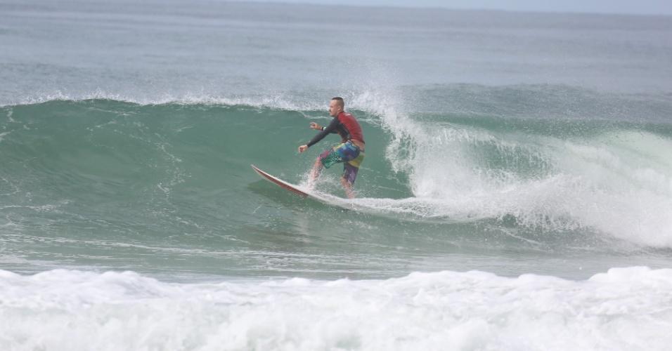 23.out.2014 - Com bermuda colorida, Paulinho Vilhena surfa na praia da Reserva, no Rio de Janeiro