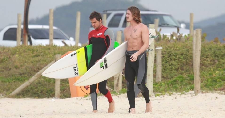 23.out.2014 - Sem camisa, Rômulo Neto chega à praia da Reserva, no Rio, para surfar, acompanhado de amigo