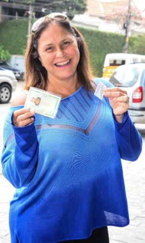 26.out.2014 - A cantora Fafá de Belem mostra seu documento e comprovante de votação, em colégio em Pinheiros, zona oeste de São Paulo