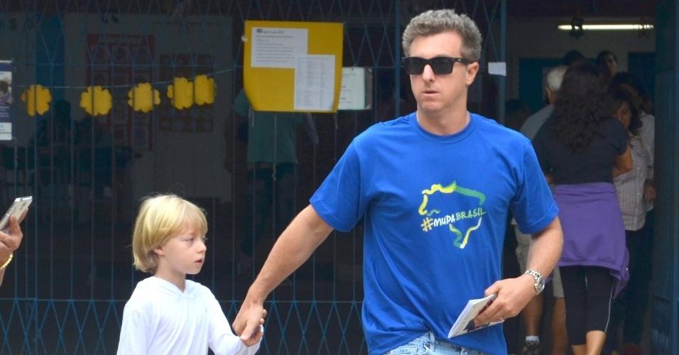 26.out.2014 - Luciano Huck vai com o filho votar na Barra da Tijuca, no Rio de Janeiro. O apresentador ainda parou para tirar foto com fãs.