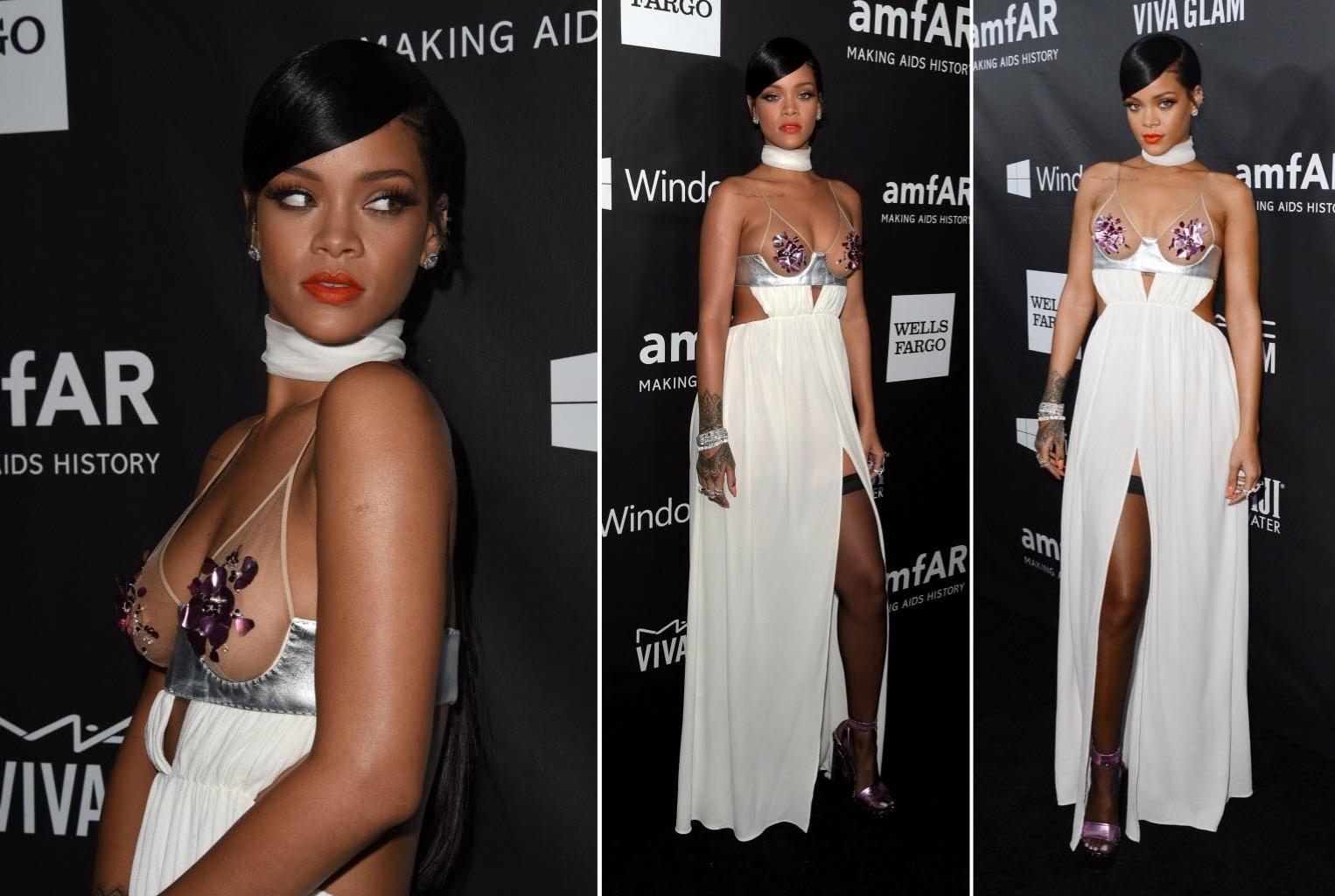29.out.2014 - Rihanna chama a atenção no baile de gala da amfAR no Milk Studios, em Los Angeles, nos Estados Unidos, na noite desta quarta-feira. Sempre polêmica, a cantora de Barbados deixou os seios à mostra e exibiu as pernas em uma grande fenda frontal no vestido branco