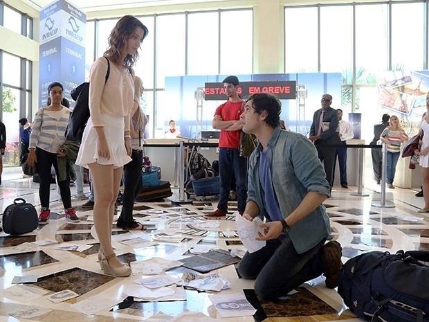 Caíque (Sergio Guizé) corre para catar seus desenhos no saguão do aeroporto. Quando se agacha para pegar um dos retratos, Laura (Nathalia Dill) pisa no papel. Caíque reclama: