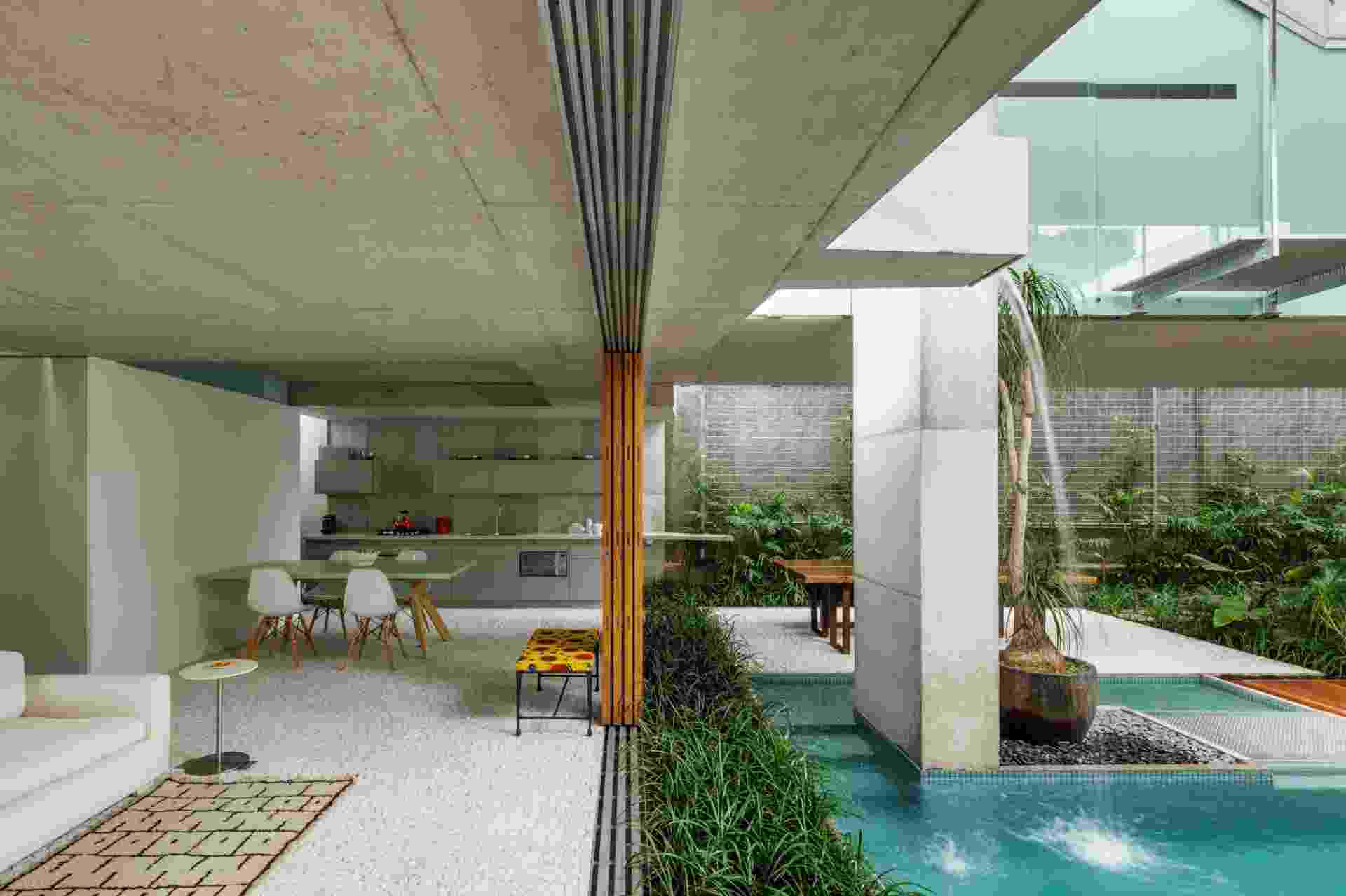 """[VENCEDOR] O Melhor da Arquitetura 2014 - categoria """"Casa Urbana - Menos de 300 m²"""": Casa de fim de semana em São Paulo - SPBR Arquitetos. Estruturada em concreto aparente, a casa respeita o limite de seis metros de altura estabelecido para o bairro, na capital paulista. No nível do solo, o pavilhão social (foto), composto por estar, jantar e cozinha, é totalmente aberto para o abundante jardim, com espelho d'água - Divulgação"""