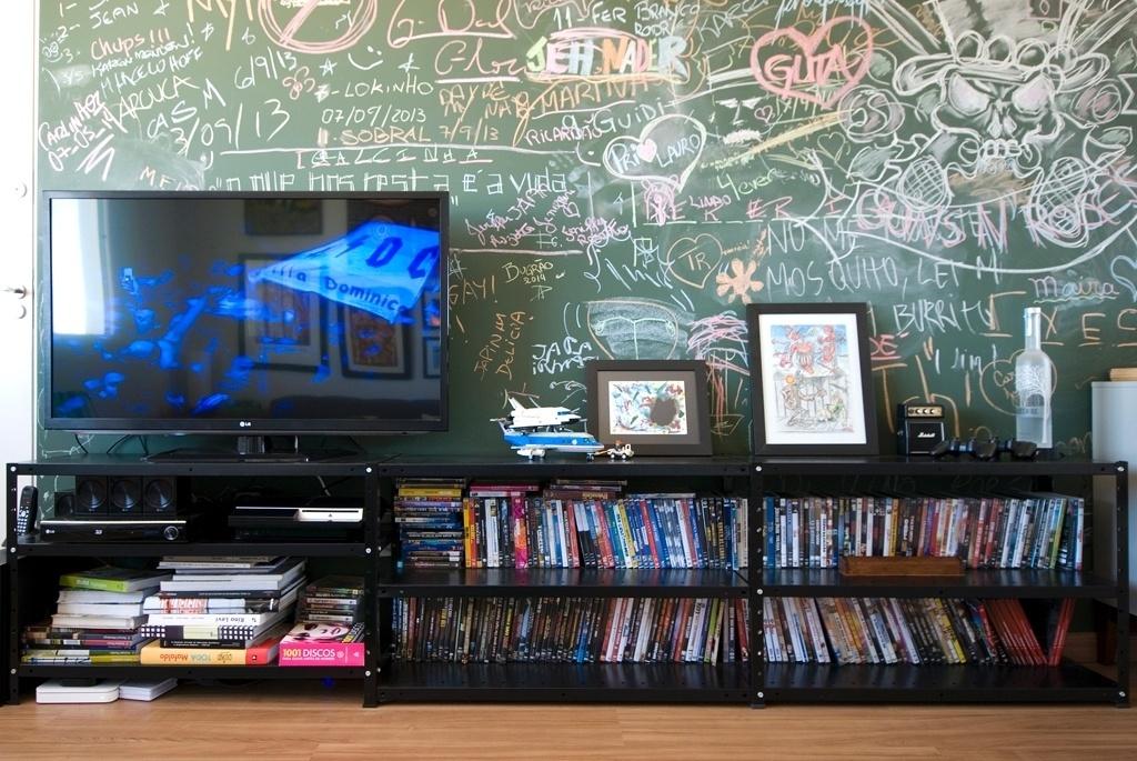No projeto do apartamento alugado, em Mogi Mirim (SP), a parede pintada com tinta lousa se tornou o elemento central e interativo da sala de estar. Nela, convidados do morador deixam seus registros divertidos e coloridos, em forma de desenhos, assinaturas e recados. O rack da TV, formado por prateleiras metálicas (Método Móveis), muito usadas em escritórios, é uma das soluções criativas e baratas do arquiteto Leandro Matsuda, que assina a decoração do imóvel