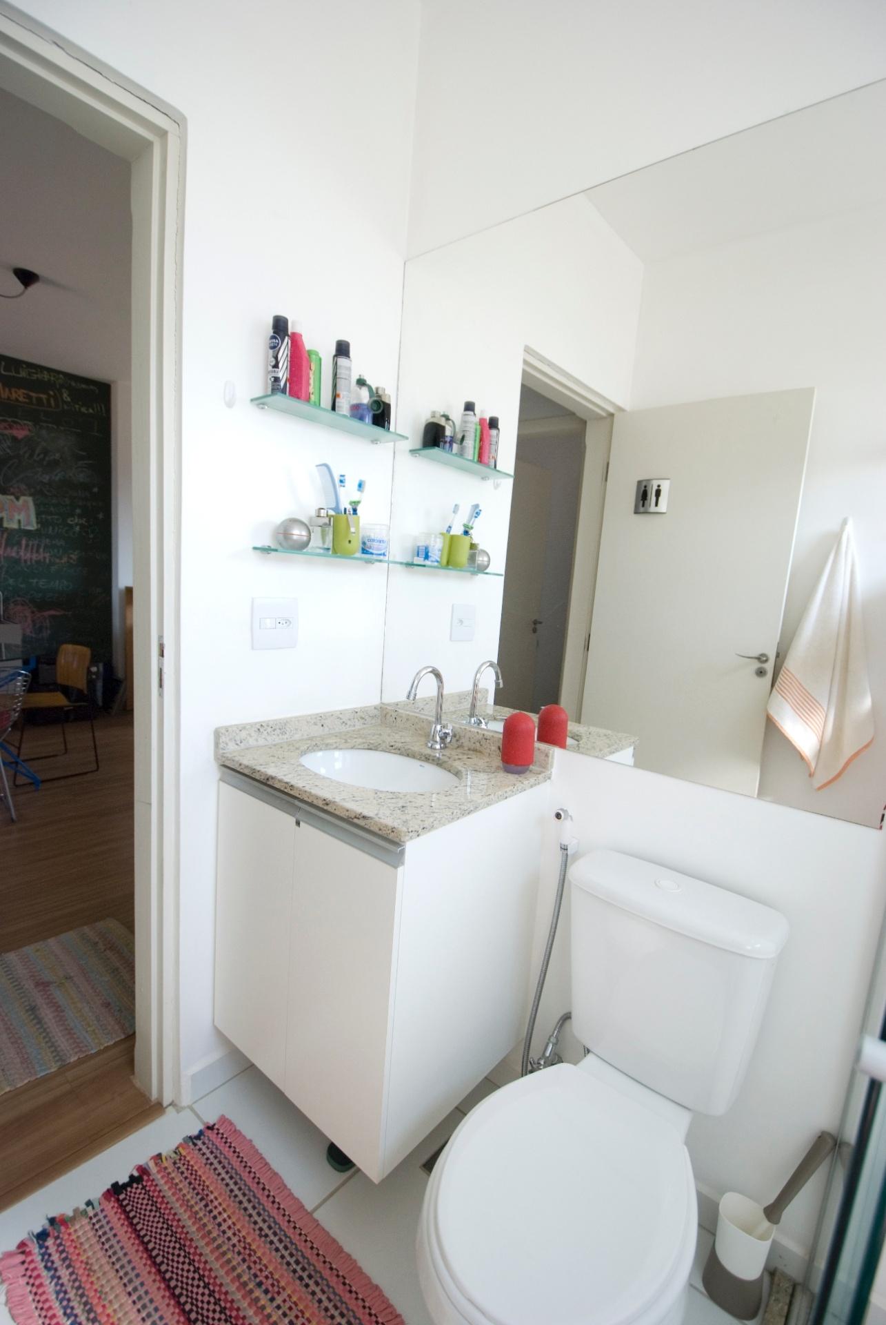 Um espelho grande se estende em uma das paredes do banheiro que ainda tem um pequeno gabinete, com cuba embutida, e prateleiras de vidro. No reflexo da porta do ambiente no espelho, é possível visualizar a simpática plaquinha que indica cômodo unissex. O apartamento em Mogi Mirim (SP) tem decoração projetada por Leandro Matsuda