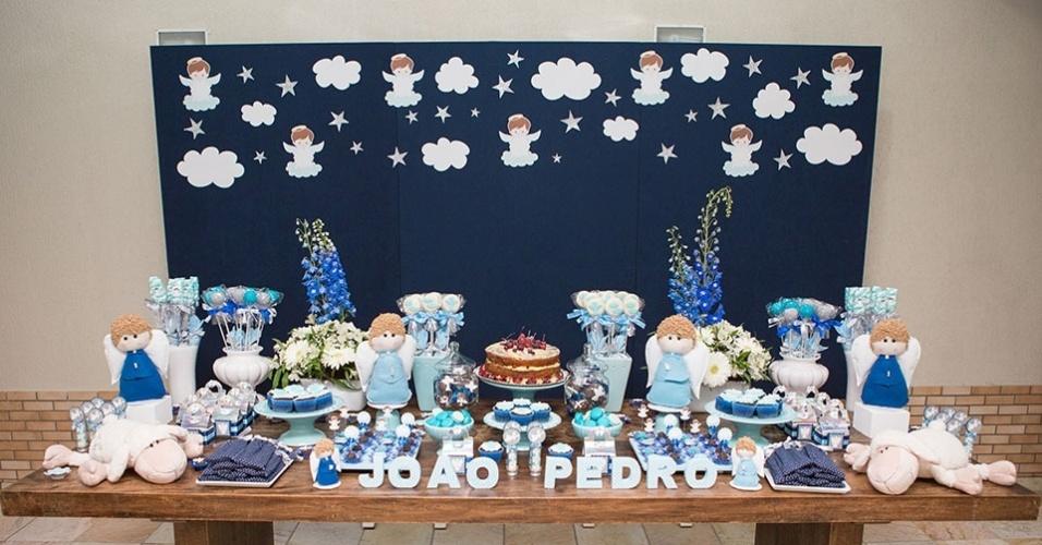 Variações da cor azul foram usadas na decoração e nas guloseimas servidas nessa festa de batizado de um menino. O painel, forrado com tecido azul marinho com aplicação de estrelas, anjos e nuvens, feitos de papel para