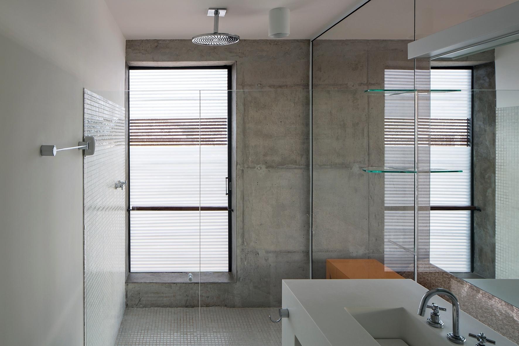 Integrado ao dormitório, o banheiro é todo branco e contrasta com o concreto aparente predominante. Revestindo o piso, pastilhas de vidro. A bancada é feita com superfície sólida mineral (Corian), do Studio Vitty; a ducha é da Deca e os espelhos são da Vidraçaria Boa Nova. A Casa Ithayê foi projetada pelo escritório Apiacás Arquitetos