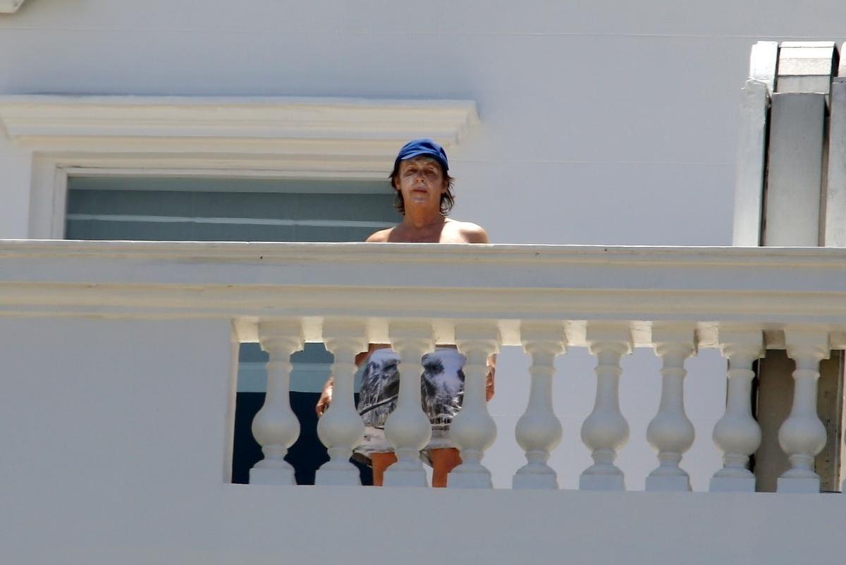 12.nov.2014 - Usando um boné azul e protetor solar, Paul McCartney se protegeu do sol do Rio de Janeiro na varanda do hotel Copacabana Palace