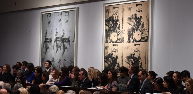 """12.nov.2014 - Pessoas participam do leilão dos quadros """"Triple Elvis"""" (à esq, ao fundo) e """"Four Marlons"""", na casa de leilões Christie""""s, em Nova York - Don Emmert/AFP"""