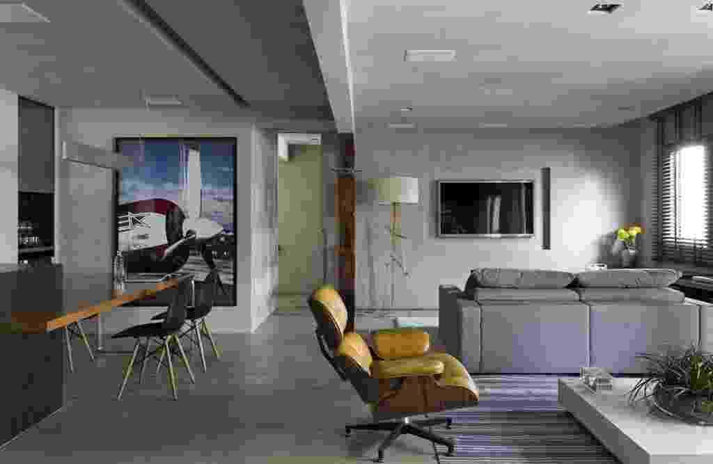 """O projeto assinado pelo arquiteto Diego Revollo tem tom urbano e um toque industrial. Nas paredes, no forro e no piso foi aplicado o revestimento cimentício da Bricolagem Brasil. O acabamento foi combinado a pitadas de azul e contraposto à madeira cumaru em tom castanho avermelhado e ao amarelo da chaise. A sugestão atendeu ao desejo do morador que prefere uma ambientação confortável. """"A ideia foi aquecer e enriquecer o ambiente, de um ponto de vista estético"""", destaca - Alain Brugier/ Divulgação"""